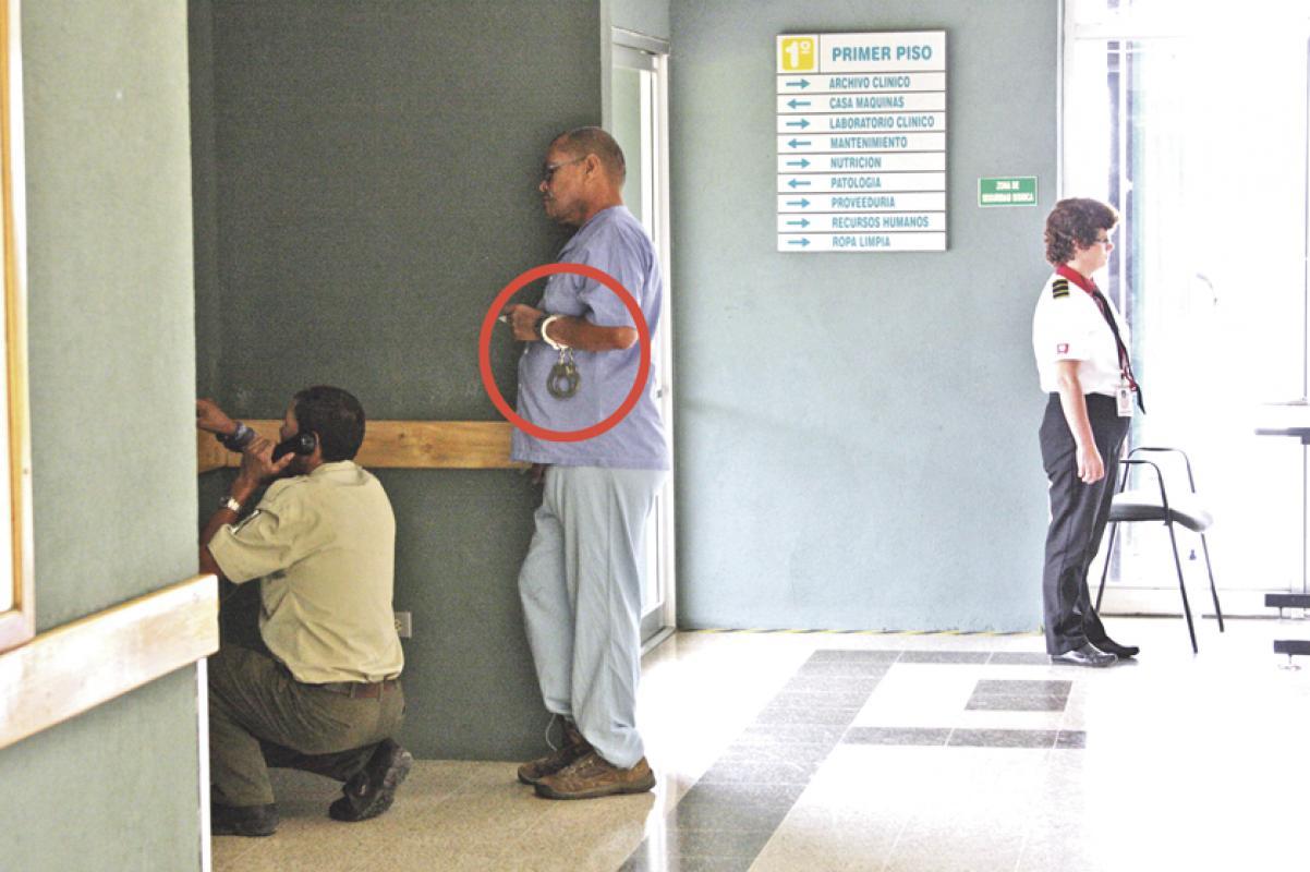 Un policía penitenciario habla por teléfono en el hospital de Alajuela mientras el reo esposado lo observa. ¿Quién cuida a quién?