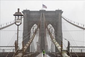 Un hombre atraviesa corriendo el puente de Brooklyn en medio de una tormenta de nieve en Nueva York, Estados Unidos