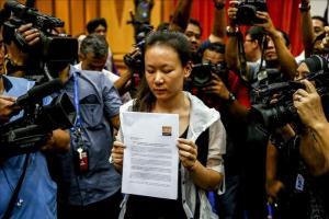 La mujer de uno de los viajeros del vuelo de Malaysian Airlines MH370 muestra una proclama escrita durante una rueda de prensa en Putrajaya