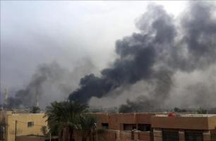 Una columna de humo se eleva por encima de varios edificios, hoy en Faluya (Irak)