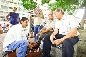 """Manuel Fresno y """"Cacao""""  Rojas conversaron con el limpiabotas Enier Serrano en el  Parque Central de San José"""