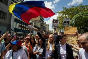 Comienza la audiencia en Caracas en la que se espera sentencia a Leopoldo López Un hombre sostiene un afiche del líder opositor venezolano Leopoldo López, este 4 de septiembre, afuera del Palacio de J
