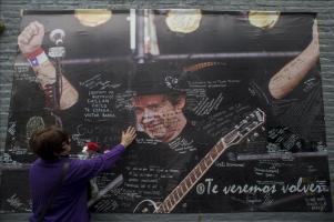 Argentina recuerda a Gustavo Cerati en el primer aniversario de su muerte Una fanática del músico argentino Gustavo Cerati lleva flores frente a un cartel con su imagen y mensajes Buenos Aires (Argent