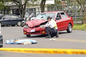 El cadáver de la anciana fue cubierto mientras un oficial de tránsito inspecciona el carro que la arrolló