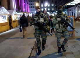 Dos soldados patrullan en el mercado navideño después de que el nivel de alerta por amenaza terrorista bajara del máximo, el 4, al nivel 3, en Bruselas, Bélgica,