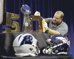 Un empleado le saca brillo al trofeo Vince Lombardi que se llevará el ganador de la edición 50 del Super Bowl (Fotos: EFE)