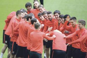 Los jugadores del Atlético de Madrid bromean durante el entrenamiento de ayer en el Allianz Arena